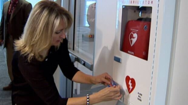 Kim Ruether adds a sticker that encourages people to use defibrillators to a device at Edmonton International Airport on Thursday.