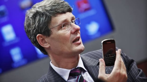 Research in Motion CEO Thorsten Heins, holding up a BlackBerry smartphone, announced a new round of layoffs last month, but hasn't said how many jobs will be cut, or where.