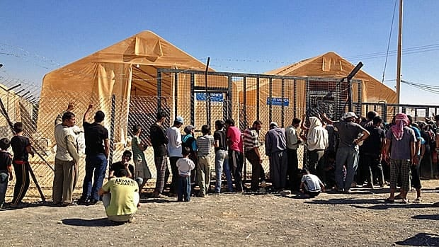 Residents at the Zataari refugee camp in Jordan line up outside the UN warehouse.