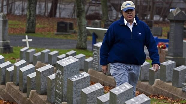 Ken Pinto strolls past grave markers of victims of the Titanic disaster in Fairview Lawn Cemetery in Halifax in December 2011. About 150 victims from the tragic sinking on April 15, 1912 were buried in Halifax cemeteries.
