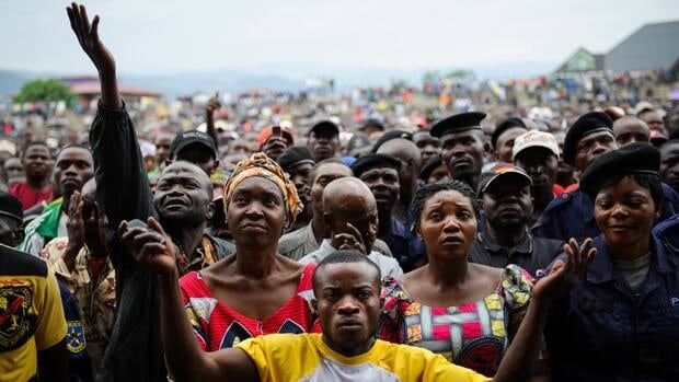 Residents of Goma listen to an M23 rebel group spokesman at the Volcanoes Stadium in the Congolese town on Wednesday.