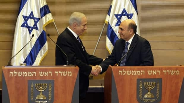Israel's Prime Minister Benjamin Netanyahu, left, and Kadima Party Leader Shaul Mofaz shake hands before holding a joint press conference announcing the new coalition government, in Jerusalem on Tuesday.