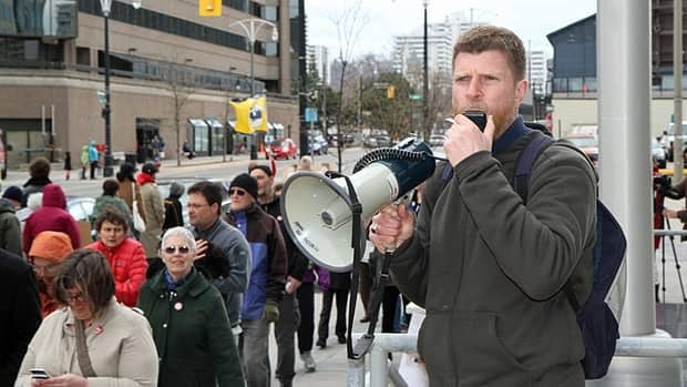 Hamiltonian Ian Wilkie addresses the crowd at an April 19 rally in support of his wife, who was deported on Saturday.