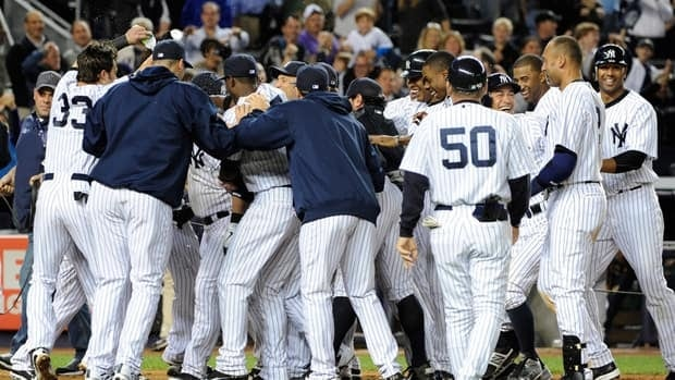 New York Yankees surround Russell Martin after he hit a solo home run off Oakland Athletics relief pitcher Sean Doolittle to give the Yankees a 2-1 win in the 10th inning on Friday in New York.