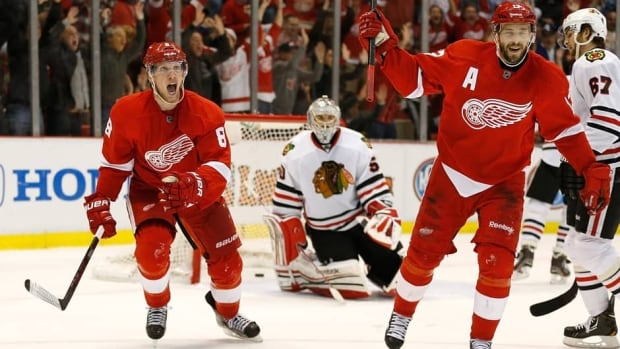 Justin Abdelkader (8) and Pavel Datsyuk (13) of the Detroit Red Wings celebrate a second-period goal by teammate Jakub Kindl (not pictured) in front of Chicago Blackhawks goalie Corey Crawford (50) in Game 4 on Thursday.