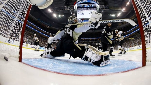 Patrice Bergeron of the Boston Bruins, right, scores a third-period goal on goalie Marc-Andre of the Pittsburgh Penguins in Game 2 of the Eastern Conference final on Monday.