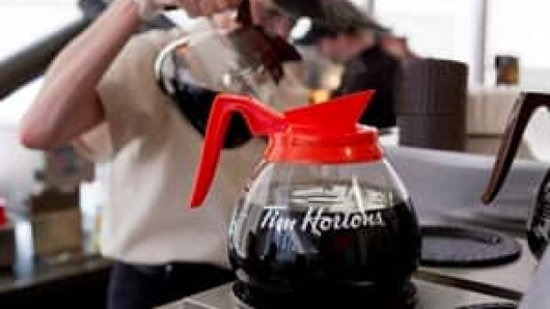 A server pours a cup of coffee in Toronto on May 10, 2012. Tim Hortons says it has raised the prices of certain baked goods and lunch items this week due to higher operating costs. THE CANADIAN PRESS/Chris Young