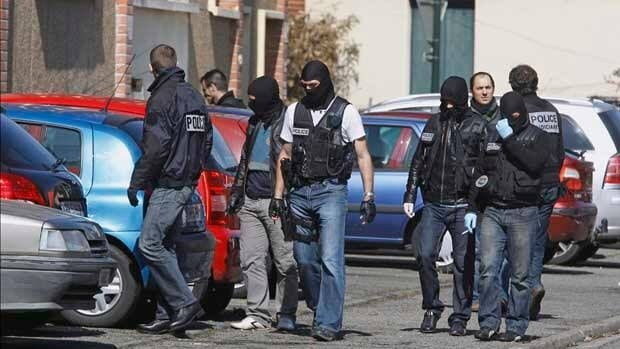 Police officers search for clues outside Mohamed Merah's apartment building in Toulouse on Friday.