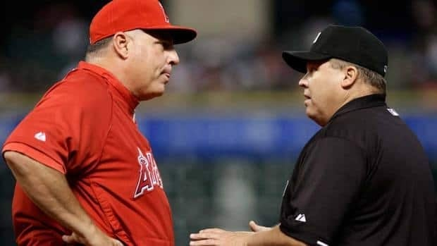Los Angeles Angels manager Mike Scioscia, left, argues a close play at first base with umpire Fieldin Culbreth om the second inning on Thursday. He'd be out late in the game to argue again, and this time MLB said the umpiring decision was wrong.