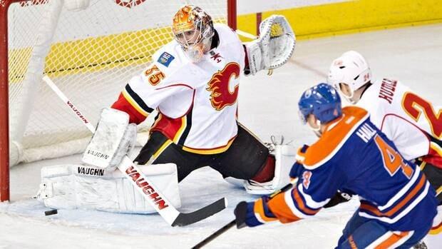 Calgary Flames goalie Joey MacDonald makes the save on Edmonton Oilers' Taylor Hall.