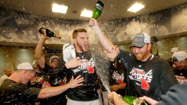 Atlanta's Freddie Freeman, centre, is doused with champagne by teammates in the clubhouse after hitting his walkoff homer to clinch a playoff spot.