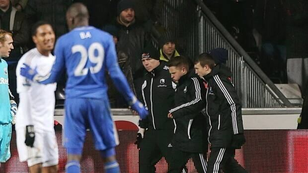 A ball boy, second from right, is whisked away after being kicked by Chelsea's Eden Hazard.