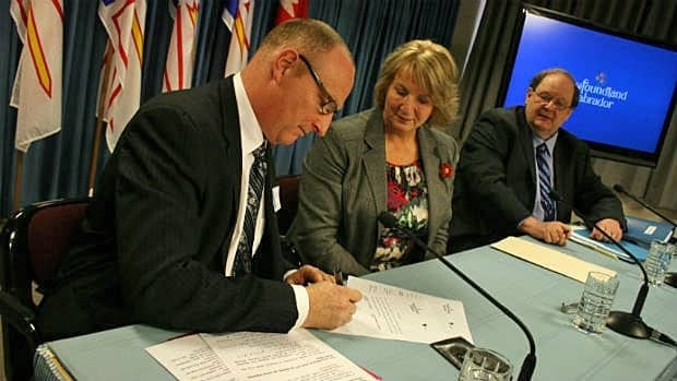 Jeff McLaughlin, vice-president of Vale's Newfoundland and Labrador operations, signs an amended deal with the provincial government as Premier Kathy Dunderdale and Natural Resources Minister Tom Marshall look on.