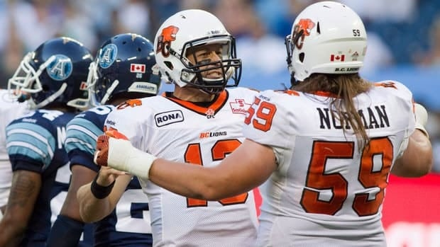 Matt Norman, right, celebrates with teammate Mike Reilly during a game against the Toronto Argonauts this season.