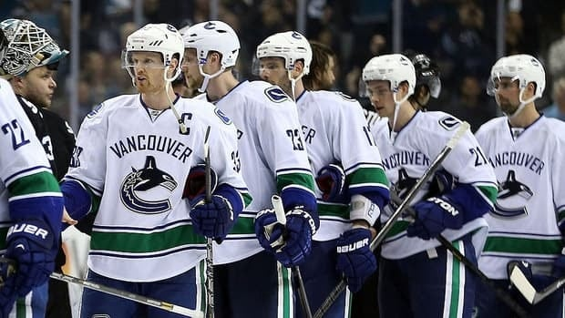 Canucks' Henrik Sedin (33) and his teammates shake hands with the Sharks after being defeated in overtime in Game 4 of their first-round Stanley Cup playoff series.