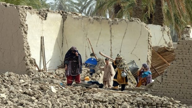 Pakistani earthquake survivors walk on the rubble of their collapsed mud houses in the Mashkail area of southwest Baluchistan province on April 17.