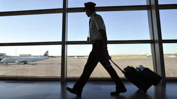 An Air Canada pilot walks to his plane at the international airport in Calgary on Sept. 20, 2011. Todd Korol/Reuters