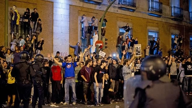 Demonstrators shout at riot policemen during a protest against spending cuts in Madrid Tuesday.