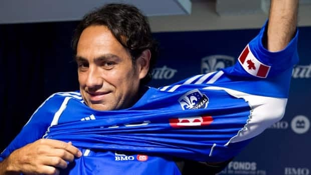 Italian defender Alessandro Nesta slips on his new Montreal Impact jersey after officially signing with the team on Friday.