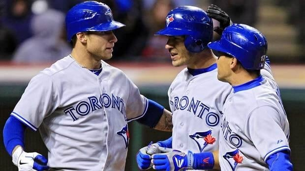 Toronto Blue Jays' J.P. Arencibia, center, celebrates with Brett Lawrie, left, and Omar Vizquel after Arencibia's three-run home run in the 16th inning of a baseball game against the Cleveland Indians Thursday.