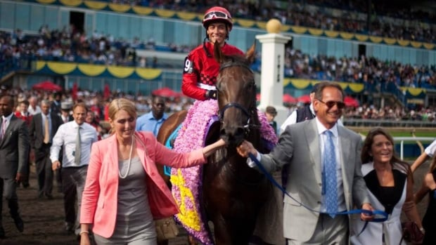 Owner Vern Dubinsky, right, and trainer Josie Carroll, left, lead horse Inglorious and jockey Luis Contreras after winning the 152nd running of the Queen's Plate in 2011.