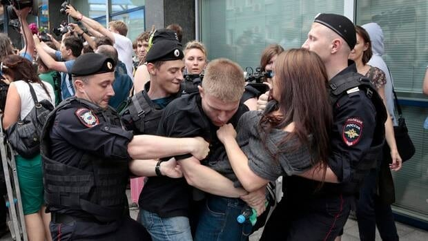 Police officers detain gay rights activists in Moscow in June before the passage of a bill that bans the distribution of information about homosexuality.
