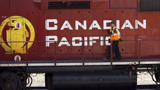 A Canadian Pacific Railway employee walks along the side of a locomotive in a marshalling yard in Calgary. Unionized workers at CP Rail have turned up the heat at the bargaining table, serving 72-hour strike notice.