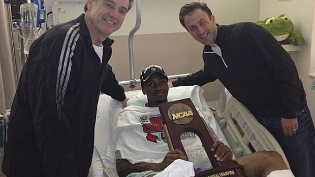 Injured Louisville guard Kevin Ware lies in a hospital bed Monday holding the NCAA Regional Championship trophy flanked by coach Rick Pitino, left, and former Louisville assistant coach Richard Pitino.