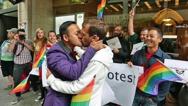 Two men participate in a kiss-in outside the Russian consulate in Vancouver to protest Russia's new anti-gay laws.