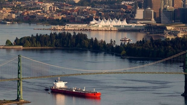 An oil tanker is guided by tugboats under Vancouver's Lions Gate Bridge at the mouth of Burrard Inlet.