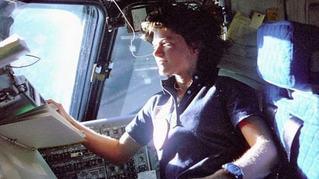Sally Ride monitors control panels from the pilot's chair on the flight deck of the shuttle Challenger in 1983.
