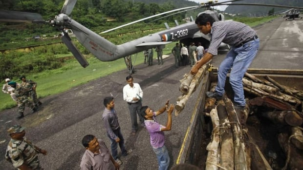 Locals in the northern Indian state of Uttarakhand unload wooden logs from a truck earlier this week. Authorities in the region conducted mass cremations Thursday of hundreds of people who were killed by devastating floods and landslides.