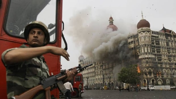 In this Nov. 29, 2008 file photo, an Indian soldier takes cover as a hotel burns during a gun battle between Indian military and militants inside the hotel in Mumbai, India. India executed the lone surviving gunman from the 2008 attack on Mumbai early Wednesday. Ajmal Kasab, a Pakistani citizen, was hung at a jail in Pune, a city near Mumbai, after India's president rejected his plea for mercy.