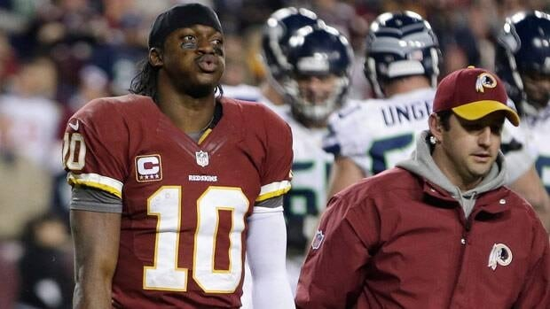 Washington Redskins quarterback Robert Griffin III walks off the field after twisting his knee during the second half of Sunday's NFL wild card playoff football game against visiting Seattle.