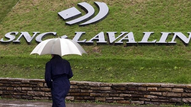 A pedestrian walks past the SNC-Lavalin Group Inc. headquarters in Montreal. A law firm is trying to bring a $1.5 billion class action suit against the company.