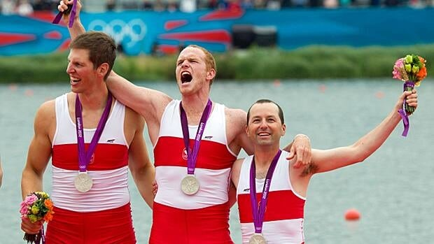 Canada's men's eight rowing team members Jeremiah Brown, Will Crothers, and cox Brian Price celebrate silver.