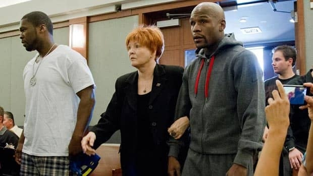 Floyd Mayweather Jr., right, accompanied by friend 50 Cent and attorney Karen Winckler, reports for jail Friday.