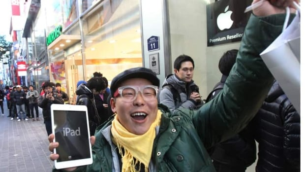 A customer in Seoul, South Korea, Song Tae-min, reacts after buying a new iPad Mini in on Friday. Apple Inc. began selling the new, smaller version of the iPad tablet, taking aim at its competitors Google and Amazon.