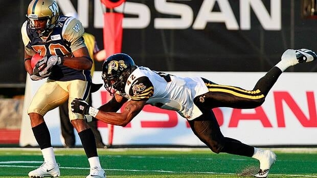 Winnipeg Blue Bombers' Quintin McCree is tackled by Hamilton Tiger-Cat Raymond Brown during second quarter CFL pre-season action in Guelph, Ontario Thursday, June 20, 2013.