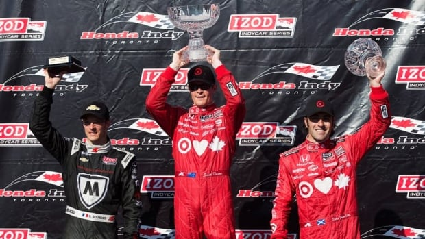 Winner Scott Dixon, centre, celebrates winning the first race at the Toronto Indy on Saturday, along with Sebastien Bourdais, left, and Dario Franchitti, right.