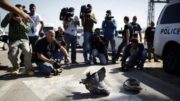 Media gather around a rocket fired from the Gaza Strip that landed in southern Israel in the first such strike since a November truce.