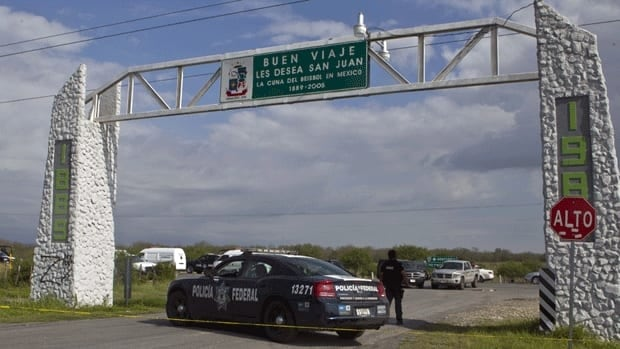 Federal police guard the area on a highway connecting the northern Mexican city of Monterrey with the U.S. border where dozens of bodies were found on the weekend.