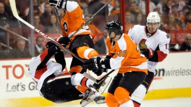Philadelphia Flyers' Harry Zolnierczyk, centre, was suspended for this hit on Ottawa Sentors defenceman  Mike Lundin, left.