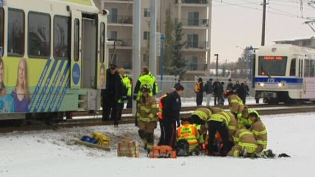 Emergency staff tend to a cyclist who was struck by an LRT train on Monday afternoon.
