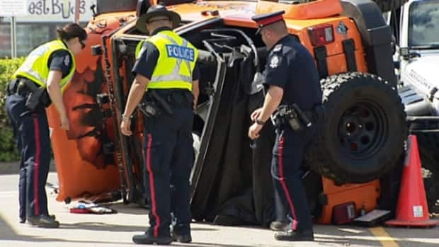 Police officers examine the vehicle that struck and killed a spectator at a Jeep event in Edmonton on Saturday.