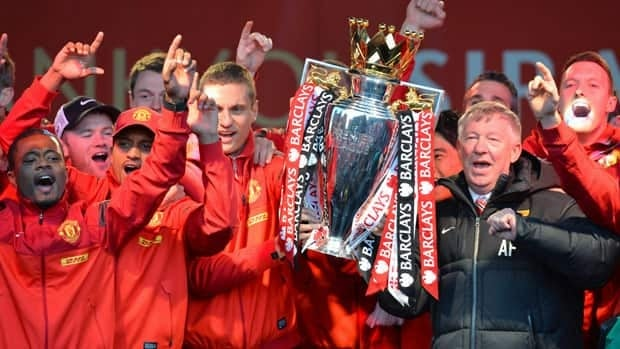 Retiring iconic Manchester United manager Alex Ferguson and his players hold the Premier League trophy outside the town hall in Manchester on Monday.