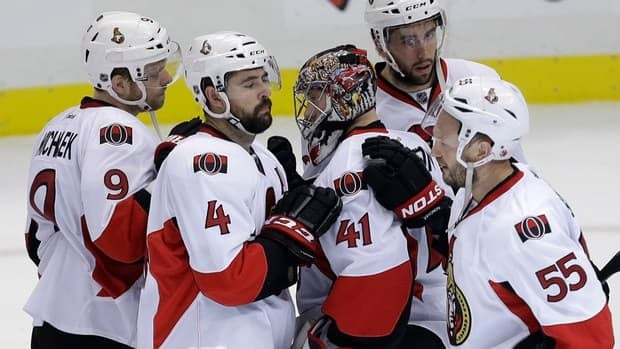 Senators goalie Craig Anderson is surrounded by teammates Milan Michalek (9), Chris Phillips (4), Sergei Gonchar (55) and Jared Cowen after being eliminated by the Penguins.