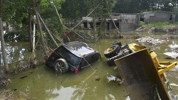 A car and a bulldozer are seen partially submerged in a flooded crop field in Dongnanzhang village of the Fangshan district in Beijing on Monday. The Chinese capital's heaviest rainstorm in six decades killed at least 37 people, flooded streets and stranded 80,000 people at the main airport, state media and the government said on Sunday.