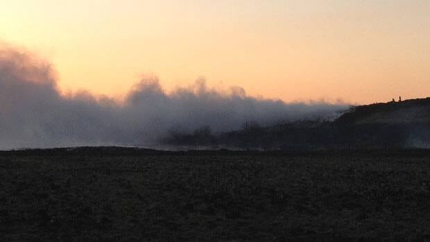 Clouds of smoke linger in the sky above Selkirk, Man., on Saturday evening, as fire crews battled a large scrapyard fire in the area.