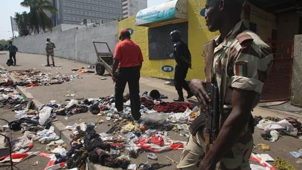 A soldier stands guard as a man walks among clothing and various items spread scattered on the pavement at the scene of a deadly stampede in Abidjan, Ivory Coast, early into New Year's Day, following a fireworks show near Felix Houphouet Boigny Stadium.